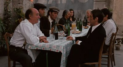 Michael siting at a table with Vitelli and Apollonia